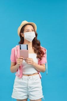 Donna che indossa una maschera igienica per prevenire il coronavirus contagioso, in possesso di passaporto, tour sicuro del resort