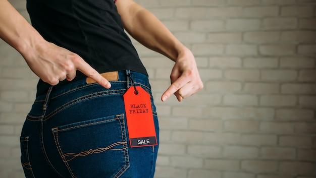 Donna che indossa jeans con etichetta black friday