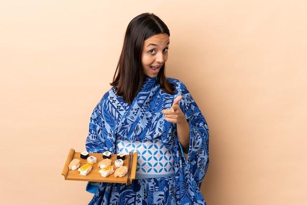 Donna che indossa il kimono e che tiene i sushi sopra la parte anteriore sorpresa e puntata isolata