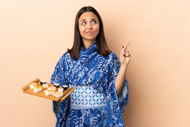 Kimono da portare della donna e giudicare i sushi sopra isolati con le dita che attraversano e che desiderano il meglio