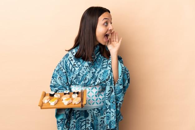 Donna che indossa kimono e che tiene i sushi sul muro gridando con la bocca spalancata al lato
