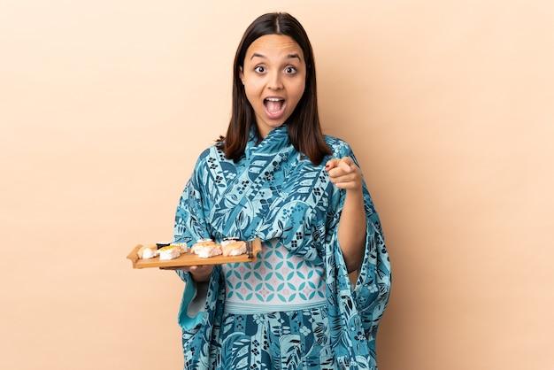 Donna che indossa il kimono e tenendo il sushi