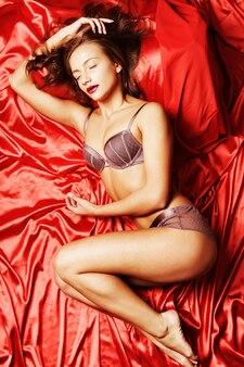 Donna che indossa lingerie posa sul letto