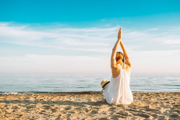 Donna che indossa un lungo abito bianco guardando il tramonto sulla spiaggia di sabbia vuota con le mani in alto. libertà, vacanza, meditazione.