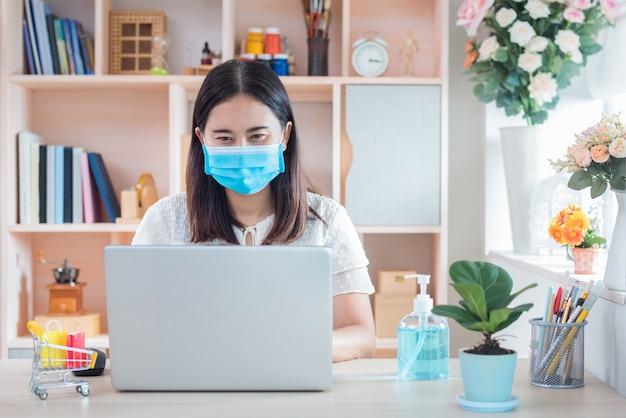 La donna che indossa una maschera attualmente lavora a casa e fa acquisti online per l'auto-quarantena durante l'epidemia di malattia da corona virus (covid-19)
