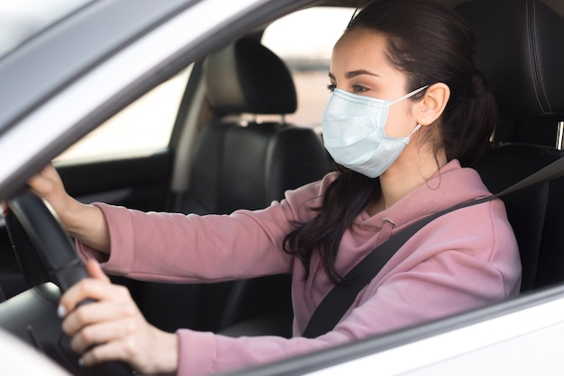 Maschera d'uso della donna dentro la sua propria vista laterale dell'automobile