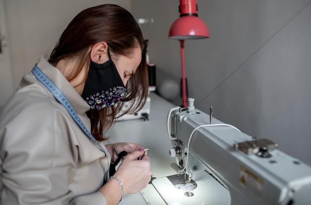 Donna che indossa una maschera e cuce le maschere su una macchina da cucire per proteggersi dal covid-19. maschera protettiva artigianale contro il virus covid19.