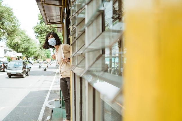 La donna che indossa una maschera aspetta l'autobus alla fermata dell'autobus
