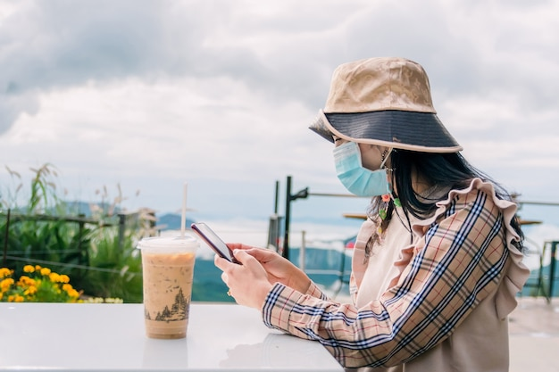 Donna che indossa una maschera mentre beve caffè durante il viaggio Foto Premium
