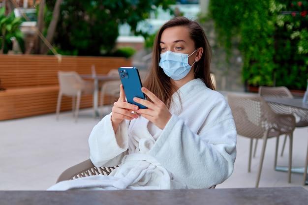 Donna che indossa una maschera medica e un accappatoio bianco utilizzando il telefono per la navigazione online e le chat durante i momenti di relax in un resort benessere durante la quarantena