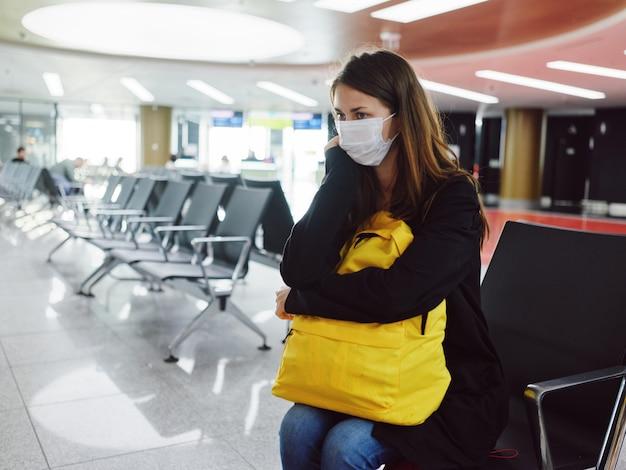 Donna che indossa una maschera medica in aeroporto con uno zaino giallo in attesa di un volo