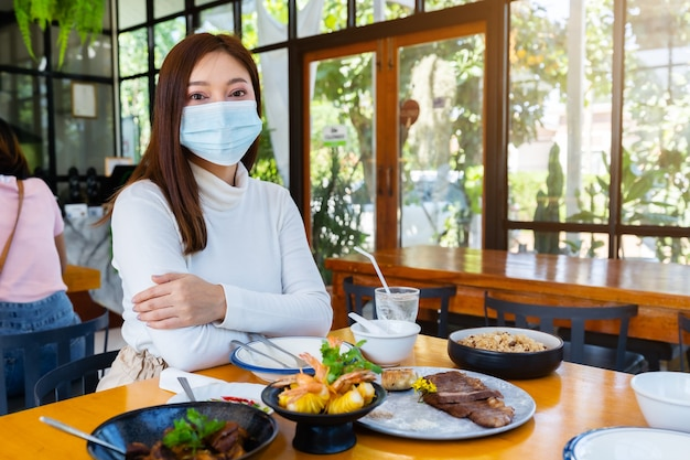Donna che indossa una maschera medica per proteggere il coronavirus nel ristorante