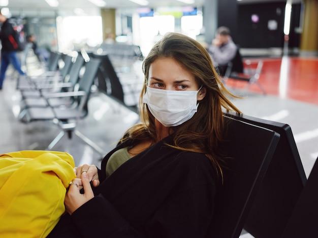 Donna che indossa una maschera medica seduta in aeroporto in attesa di uno zaino giallo di volo