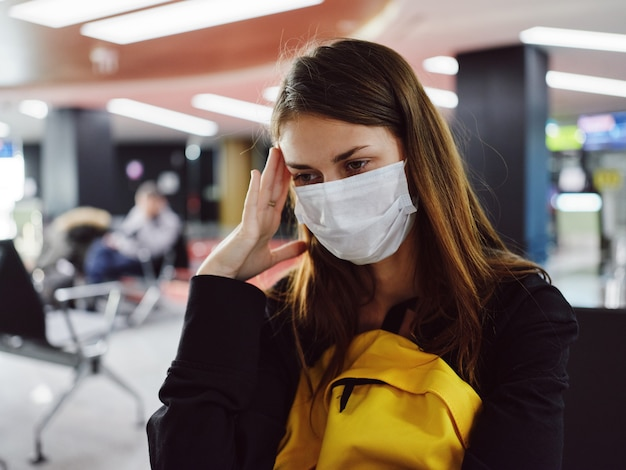 Donna che indossa una maschera medica seduta in aeroporto in attesa stanca