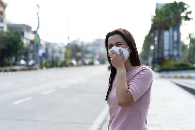 Donna che indossa una maschera protettiva per coronavirus e combattimento pm 2.5