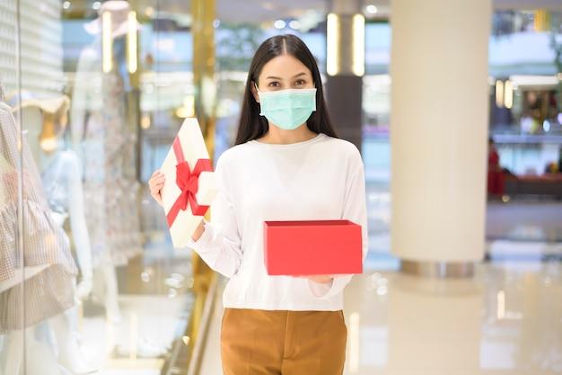 Una donna che indossa una maschera protettiva in possesso di una confezione regalo nel centro commerciale, shopping sotto la pandemia covid-19, il ringraziamento e il concetto di natale.