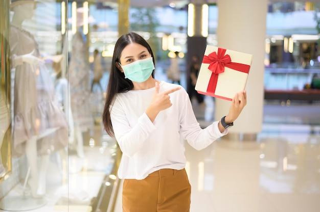 Una donna che indossa una maschera protettiva in possesso di una confezione regalo in un centro commerciale, shopping sotto la pandemia covid-19
