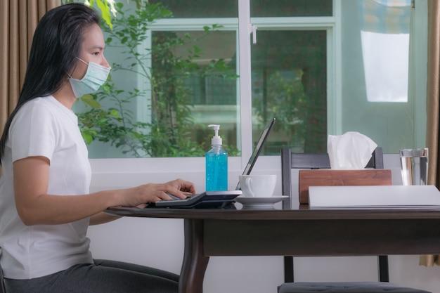 Donna che indossa una maschera protettiva usando il portatile a casa, lavorando da casa. quarantena per coronavirus.