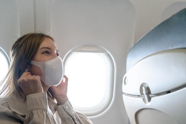 Donna che indossa maschere protettive in aereo