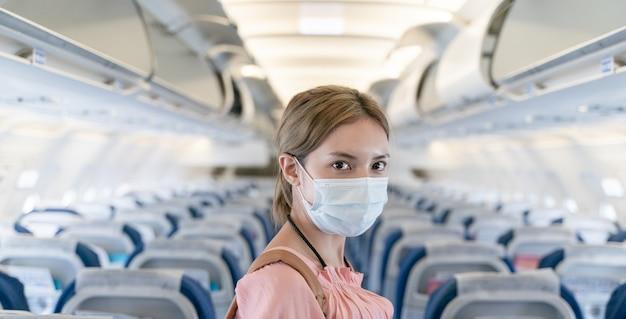 Donna che indossa maschere protettive che cammina a bordo di un aereo