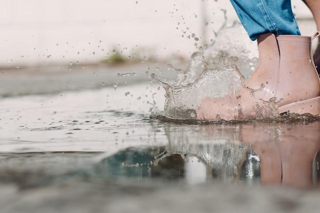 Donna che indossa stivali di gomma da pioggia camminando correndo e saltando nella pozzanghera con spruzzi d'acqua e gocce sotto la pioggia autunnale.