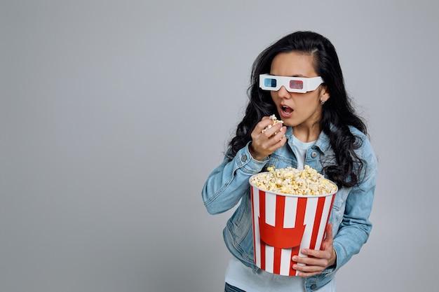 Donna che indossa occhiali rosso-blu 3d e mangiare popcorn dal secchio mentre si guarda un film isolato su grigio