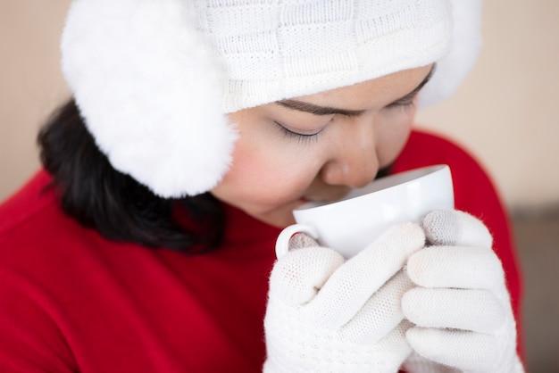 Donna che indossa un maglione rosso e beve il caffè nel soggiorno di casa nella notte di natale