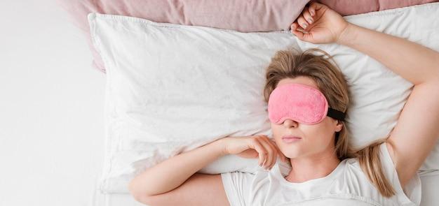 Donna che indossa una maschera per dormire sulla sua distesa piatta occhi