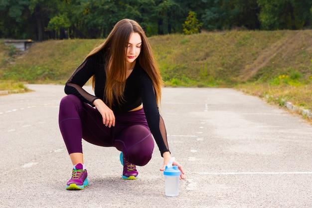 La donna che indossa abiti sportivi fa una pausa per bere acqua.