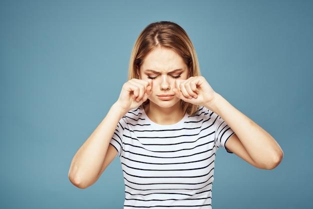 Donna che indossa la maglietta a strisce ritagliata vista blu isolato espressione facciale dispiaciuta.