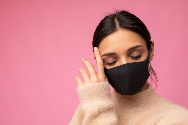Donna che indossa una maschera protettiva alla moda, in posa su sfondo rosa. accessorio di moda alla moda durante la quarantena della pandemia di coronavirus. close up ritratto in studio. copia, spazio vuoto per il testo.