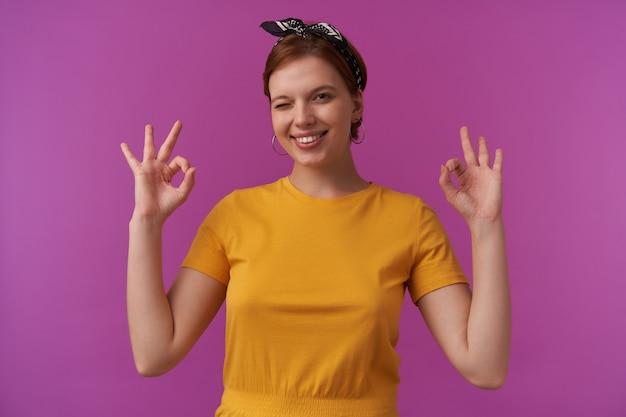 Donna che indossa una maglietta gialla estiva elegante e bandana nera emozione sorridente bel viso con trucco naturale che ti sorride e fa l'occhiolino con le braccia ok dita sul muro viola