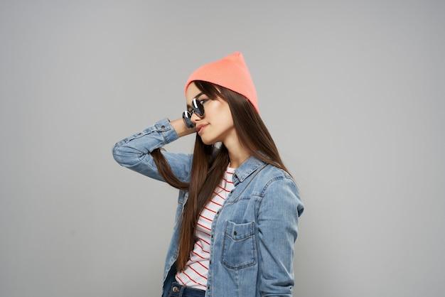 Donna che indossa occhiali da sole cappello rosa in posa studio stile moderno