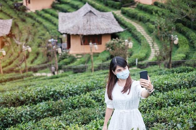 Donna che indossa la maschera chirurgica e utilizza lo smartphone mobile nel bellissimo giardino del tè