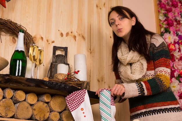 Donna che indossa un maglione che dà una sbirciatina all'interno della calza di natale