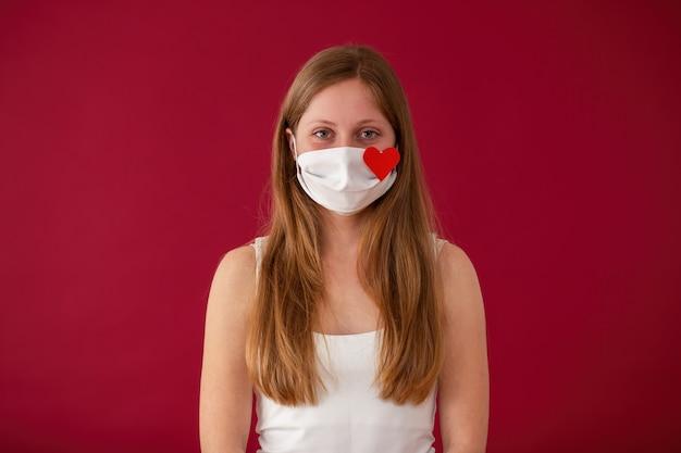 Donna che indossa la maschera per il viso di panno bianco ed esamina la macchina fotografica dalla vista frontale su sfondo rosso.