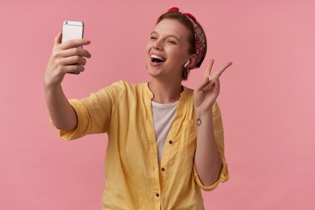 Donna che indossa t-shirt bianca e camicia gialla e bandana rossa gesticola al telefono in posa sul rosa