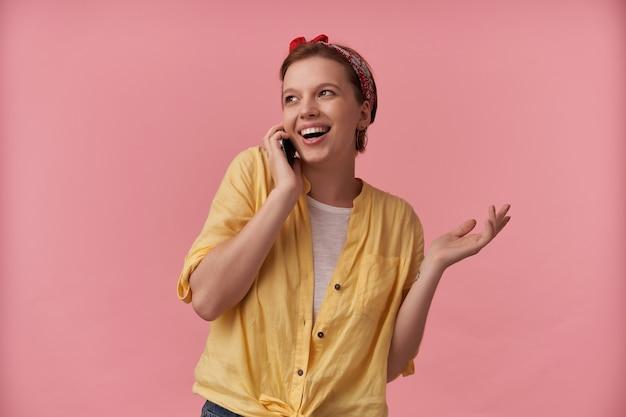 Donna che indossa camicia gialla e bandana rossa con le braccia gesticola al telefono sorridente da parte posa isolata sul rosa