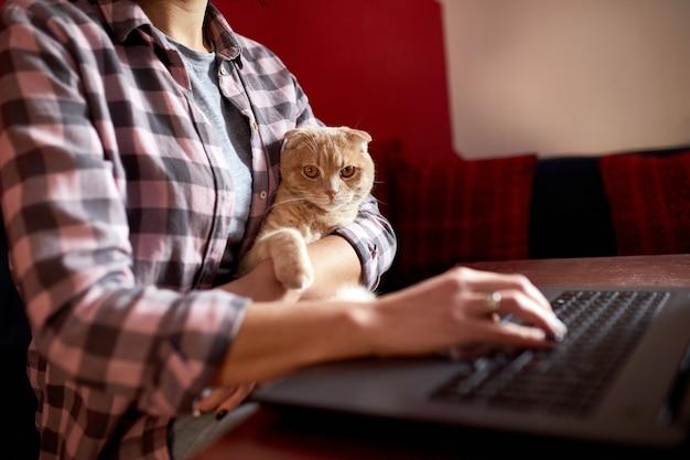 La donna indossa uno stile comodo, lavora su un taccuino nero e tiene in mano un gatto