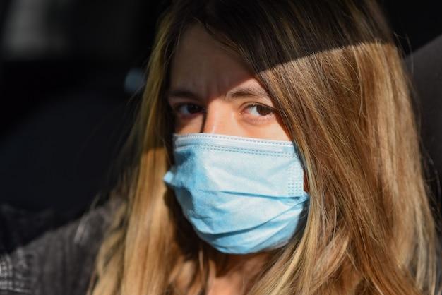 La donna indossa una mascherina medica perché l'inquinamento atmosferico o il virus è un'epidemia in città.