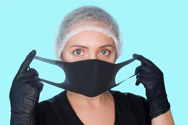 La donna indossa una maschera medica. ragazza in guanti protettivi e un berretto