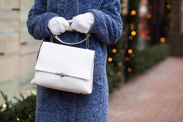 La donna indossa un abito invernale alla moda che cammina in città