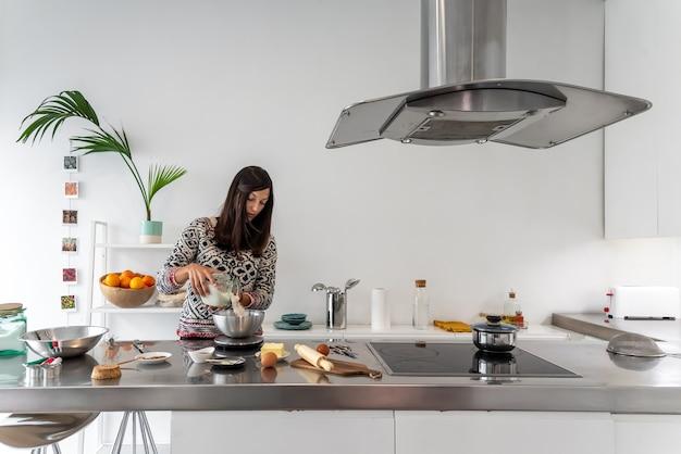 Donna che pesa farina per preparare i biscotti fatti in casa
