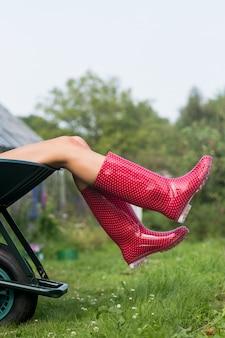 Donna in stivali di gomma in carriola
