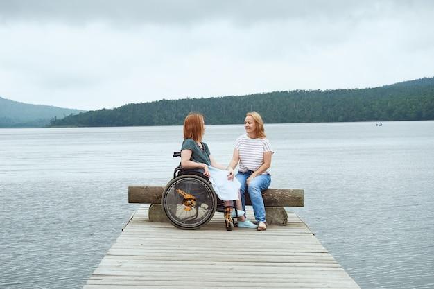Una donna su una sedia a rotelle comunica con la sua amica seduta su una panchina sullo sfondo di un bellissimo paesaggio marino