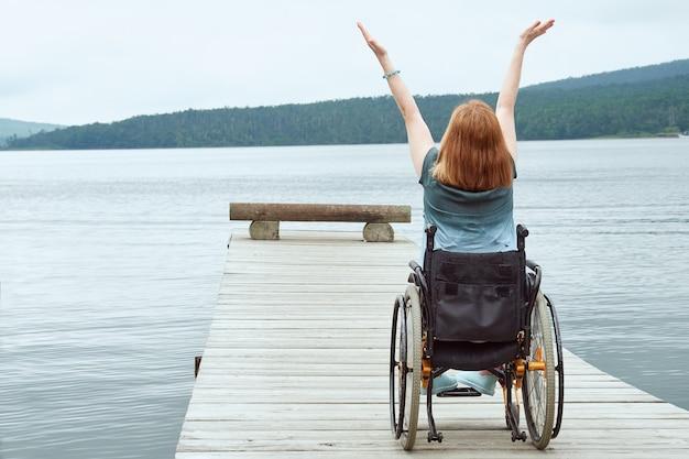 Donna in sedia a rotelle che gode della vista del mare alzando le braccia.