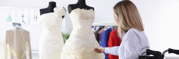 La donna in sedia a rotelle esamina l'abito da sposa nel concetto di abiti da sposa di cucito del salone