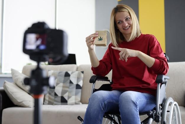 La donna in sedia a rotelle tiene il sacchetto di marijuana e spara al video blog