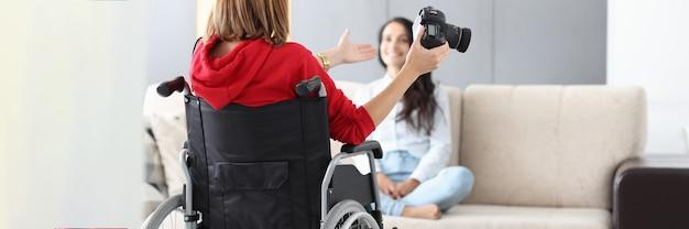 La donna in sedia a rotelle tiene la macchina fotografica e prende la foto del modello