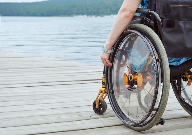 Donna in sedia a rotelle che guarda il mare, parte dell'immagine, con spazio di copia